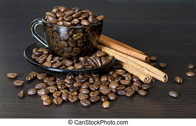 Coffee beans in a cup on dark background.