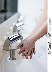 Washing hands in a public restroom focus on the tap, hands...