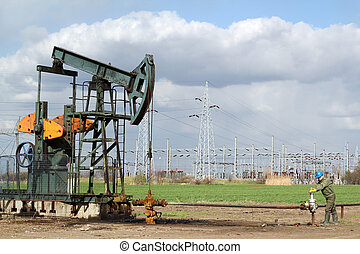 oil field with pumpjack and oil worker