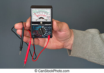 multimeter in a hand - analog multimeter with wires in a...
