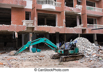Old excavator near a ruined building