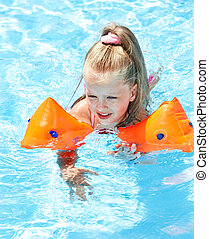 Child with armbands playing in swimming pool.