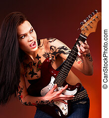 Aggressive girl with tattoo playing guitar - Aggressive...