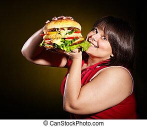 Woman eating hamburger. - Overweight woman eating hamburger.