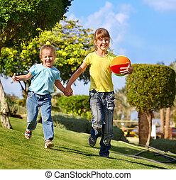 Children running in park. - Children running with ball in...