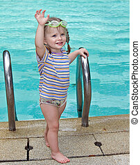 Baby in goggles leaves pool. - Baby in protective goggles...