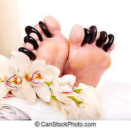 Woman receiving stone massage on feet - Woman receiving hot...