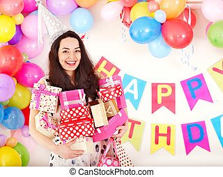 Woman holding gift box at birthday party. - Young woman...