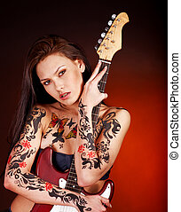 Aggressive girl with tattoo playing guitar. - Aggressive...