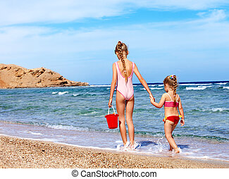 Children holding hands walking on the beach Rear view