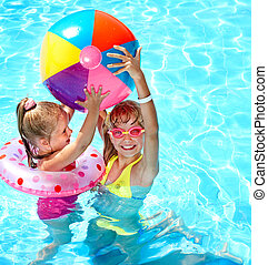 Child playing with ball in swimming pool - Child playing in...