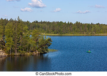 boat on the lake in the summer - the fisherman in the rubber...