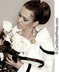 Fashion young woman with hairstyle and roses in hands
