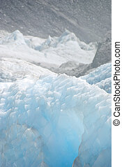 Bluish glacier and blurred gray rocks - Shiny turquise ice...
