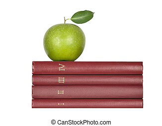 Green apple on pile of books on white background
