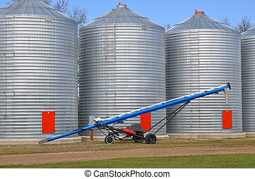 Auger in front of farm grain bins. - A blue auger sitting in...