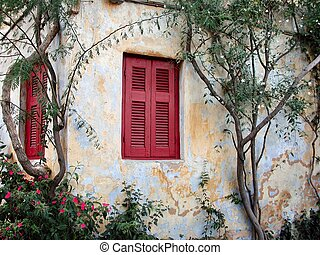 Colorful red shutters on the side of a old buiding in Greece...