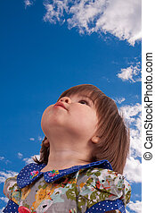 expectation - the little girl looks up at a blue sky with...