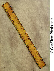 Vintage ruler and paper - An old wooden ruler lying on a...