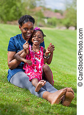 Adorable african mother with her daughter in the garden -...