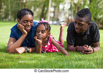 Adorable african mother with her childrens in the garden -...