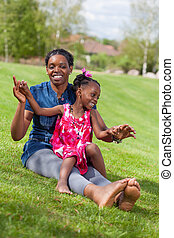 Adorable african mother with her daughter in the garden