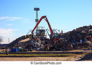 Metal scrap yard - Mechanical crane grabber working in a...