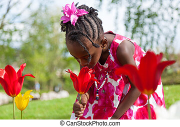 Cute little african american girl playing in the garden -...