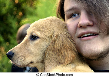 Teen Boy And Golden Puppy 1 - Closeup of a smiling teenage...