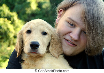Teen Boy And Golden Puppy 2 - Closeup of a smiling teenage...