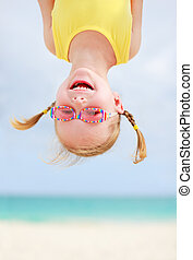 Happy little girl upside down - Adorable little girl hanging...