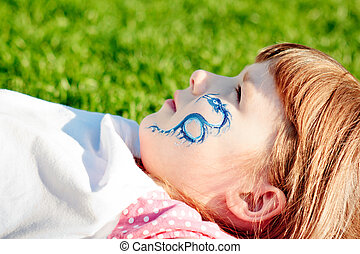 Portrait of a young girl with blue dragon on her face lying...