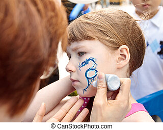 Face art - Young girl with a blue dragon painted on her...