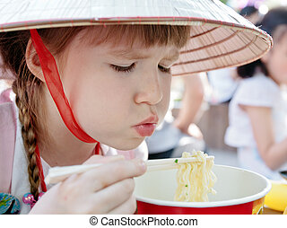 Young girl eating korean-style spaghetti in restaurant -...