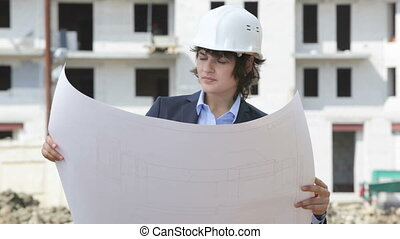 Onsite - Business woman in hardhat holding a construction...