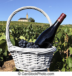 wine and church - bottle of wine in basket in France