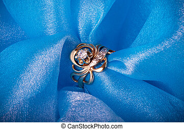 Golden jewelry ring on blue