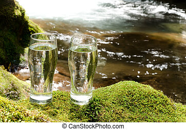 Brook and two glasses - Flow of brook and two glasses water...