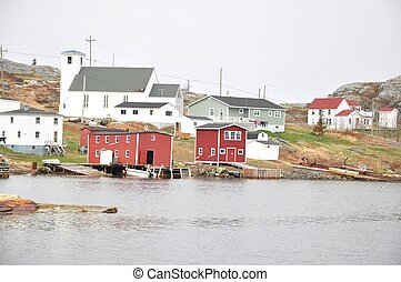 rural community in Newfoundland - red stages and church in...