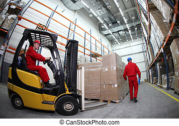two workers work in storehouse - two workers in red uniforms...