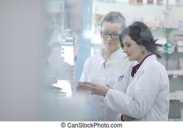 team of pharmacist chemist woman in pharmacy drugstore -...