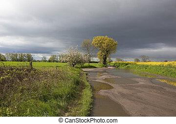 rainy countryside - a muddy farm track through an arable...