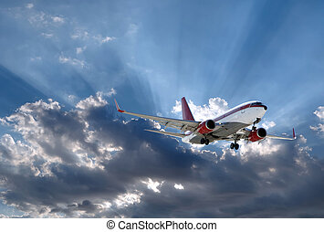 airplane and sun behind - a plane above Sun rays going...