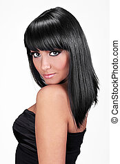 Portrait of beautiful young woman with straight black hair posing isolated on white background