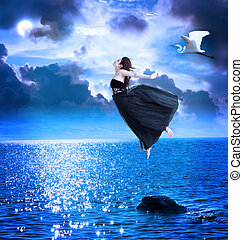 Beautiful girl jumping into the blue night sky with white...