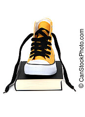 Yellow sneaker on black book