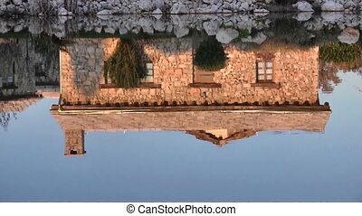 Reflection of stone house on water