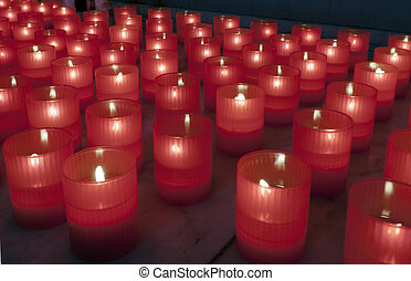 lighted candles in the red container in a church