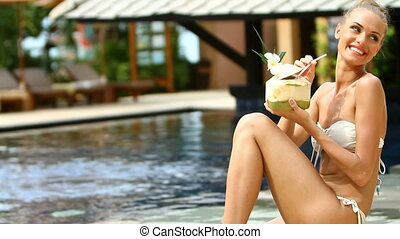 Beautiful girl sitting at the edge of swimming pool and...