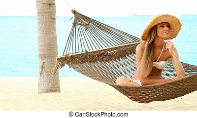 Happy woman on hammock at the exoti - Happy woman it sitting...